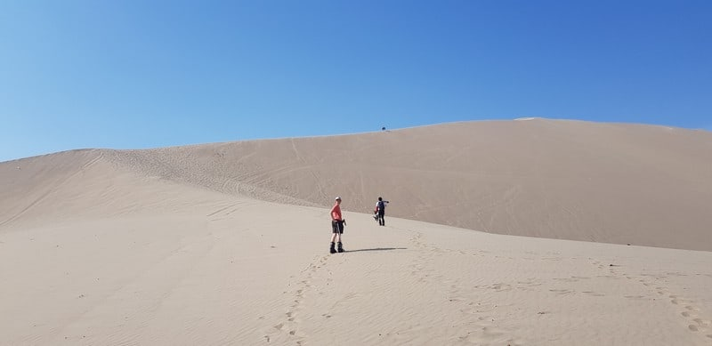 hiking up the dunes in Huacachina Peru